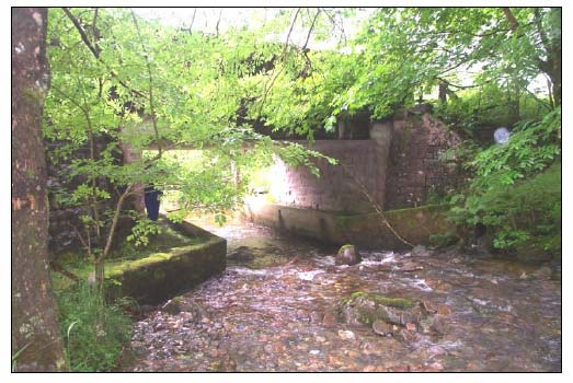 Figure 3.1 View looking downstream to Allt Fhiodhan Bridge, note the reduction in channel capacity and the presence of the riffle within the concrete foundations immediately upstream of the bridge.