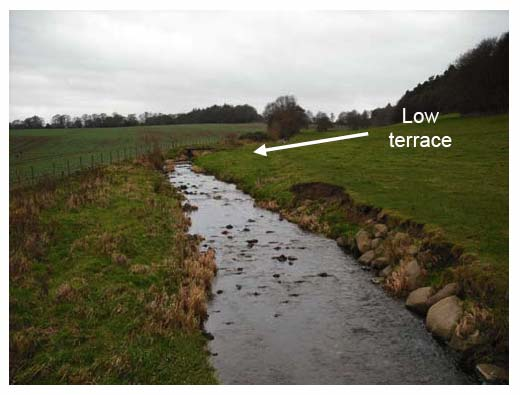 Photograph 3.6: Upstream view of Niddry Burn illustrating local erosion and protection